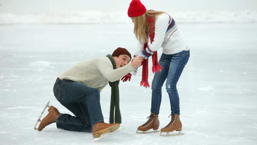 young woman helping boyfriend get up after falling while ice skating