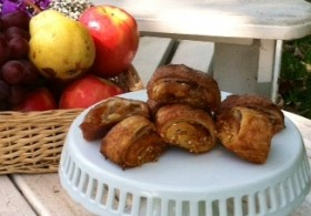 Rugelach pastry on a white pedestal with a basket of apples in the background