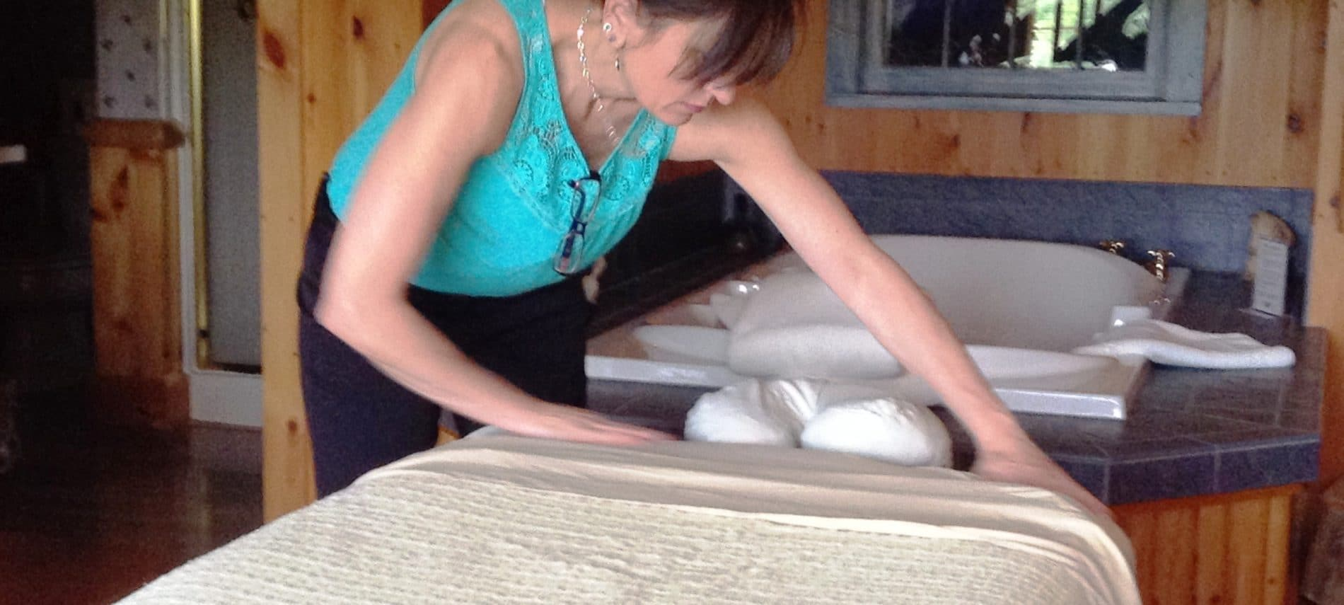 Massage therapist making up spa bed in Cedar Glen Guestroom