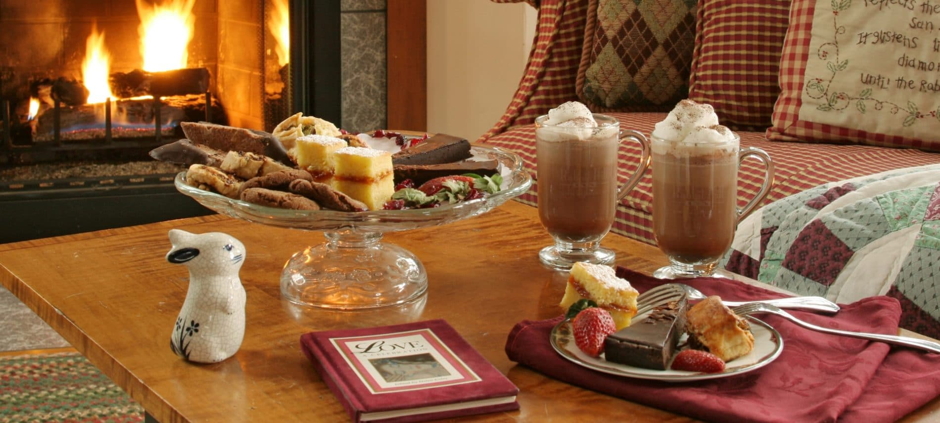 two cups of cocoa and sweets on a table in front of a fire