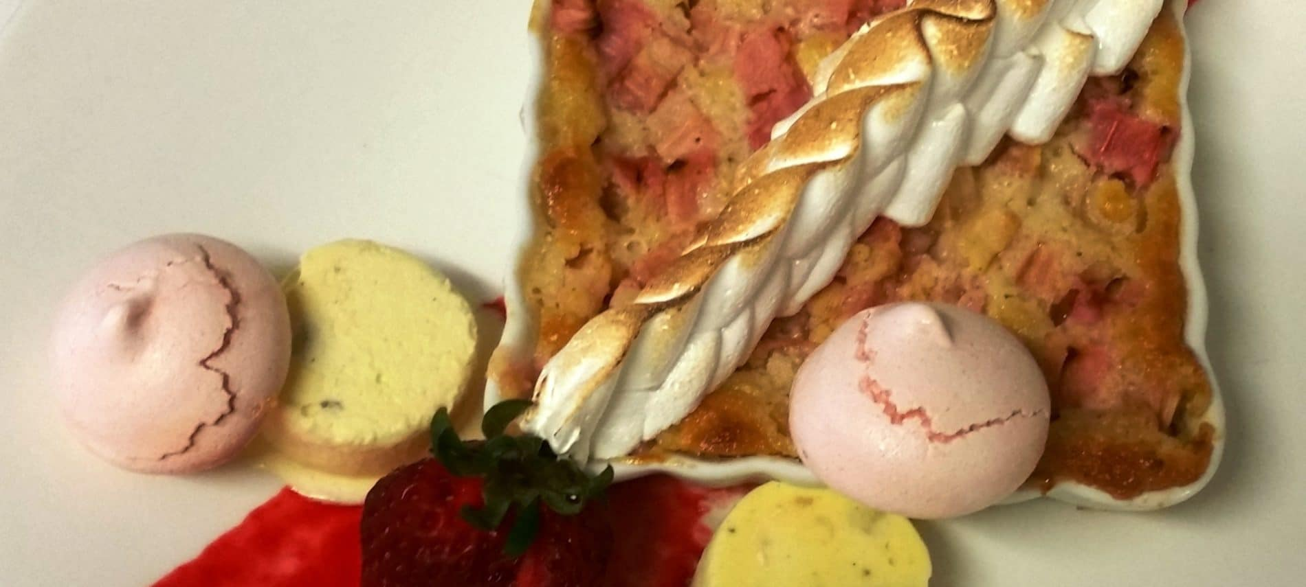 Rhubarb custard dessert served with saffron-cardamom-pistachio kulfi , rose meringue , and raspberry coulis