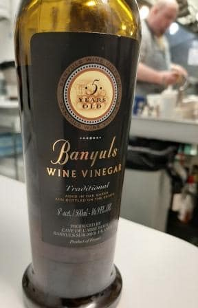 a bottle of Banyul vinegar with chef cooking in the background