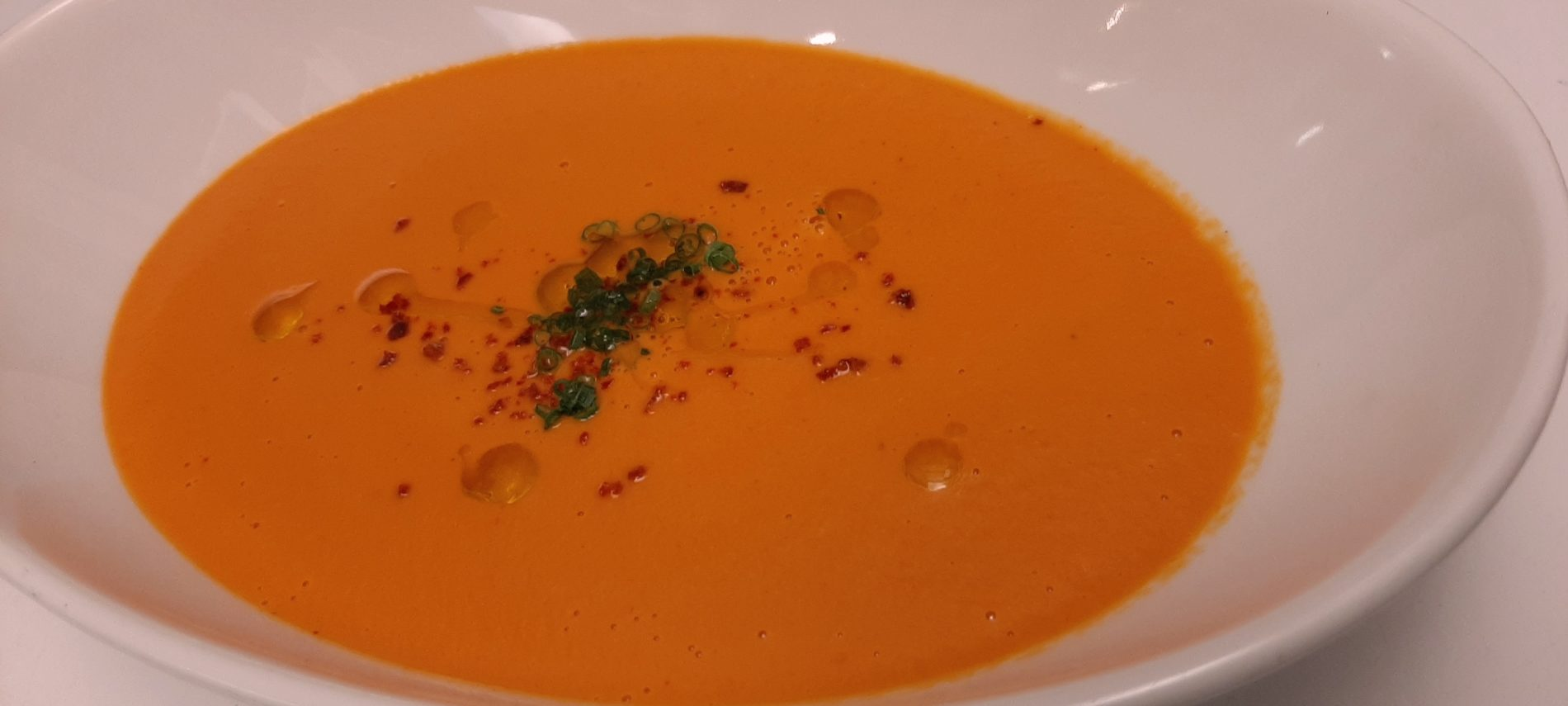 a white bowl filled with Tomato bisque soup sprinkled with sliced chives and drizzled with olive oil