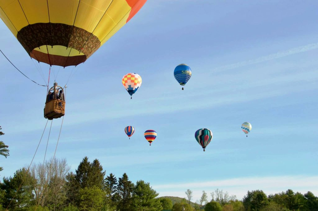 Several Hot Air Balloons in the sky in Vermont Boland Balloons Post Mills Air field