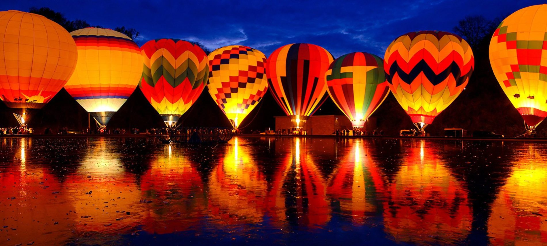 night scene of illuminated colorful balloons along a lake in Quechee vermont
