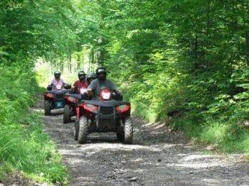 three people ATVing through the woods
