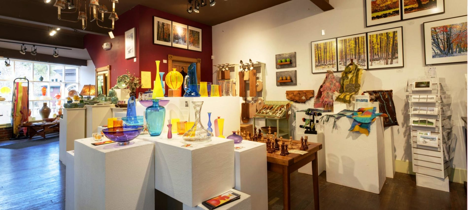 Variety of hand crafted glassware, wooded items, and paintings on display at a gallery