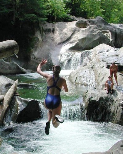 girl jumping in the water at a Swimming hole in Vermont
