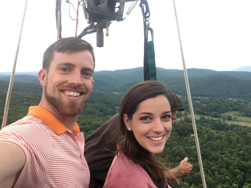 young smiling couple with balloonist high above Vermont in a balloon