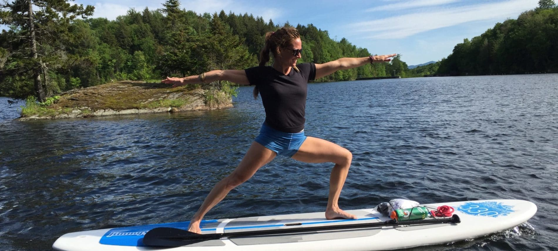 woman standing on a paddle board on the the water