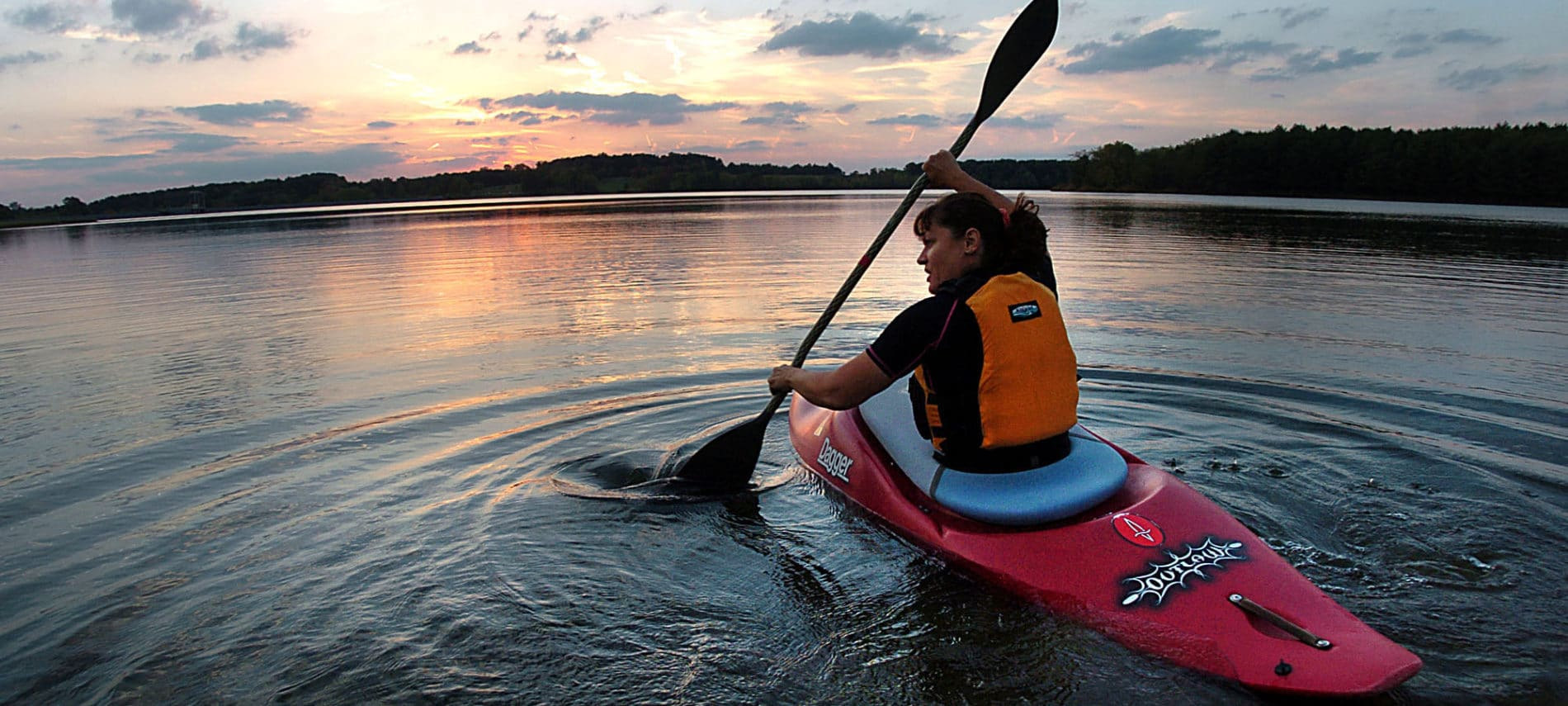 girl paddling a kayak on the river at sunset