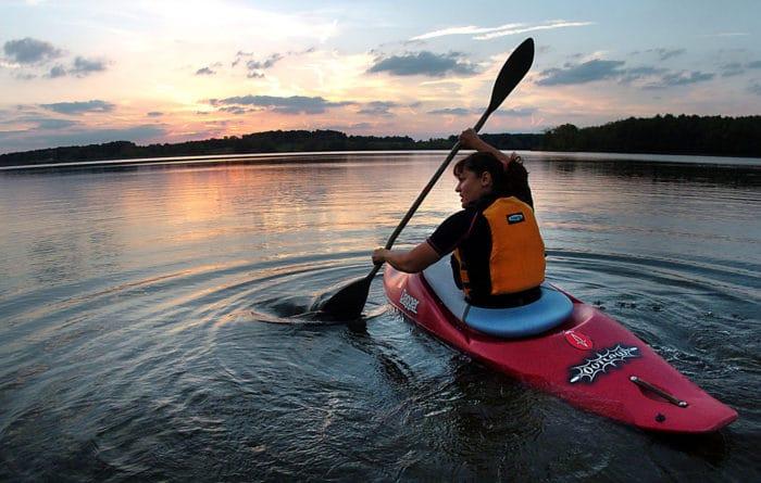 girl paddling a kayak on the river at sunset