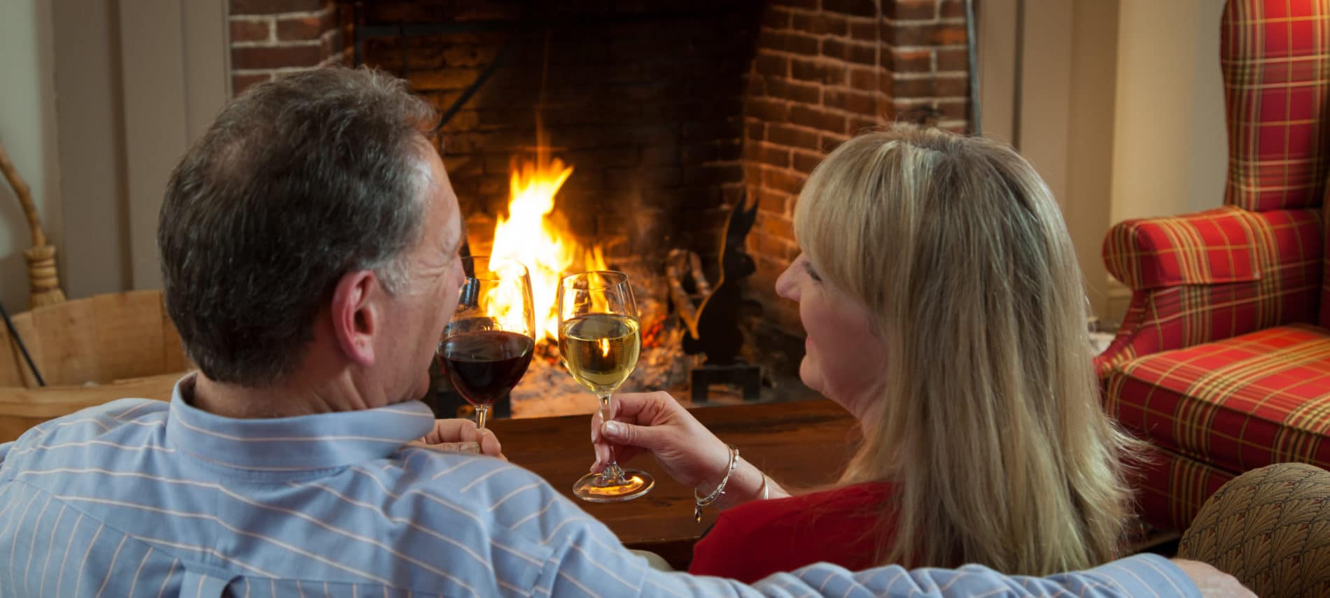 Couple toasting each other with wine in front of a fireplace