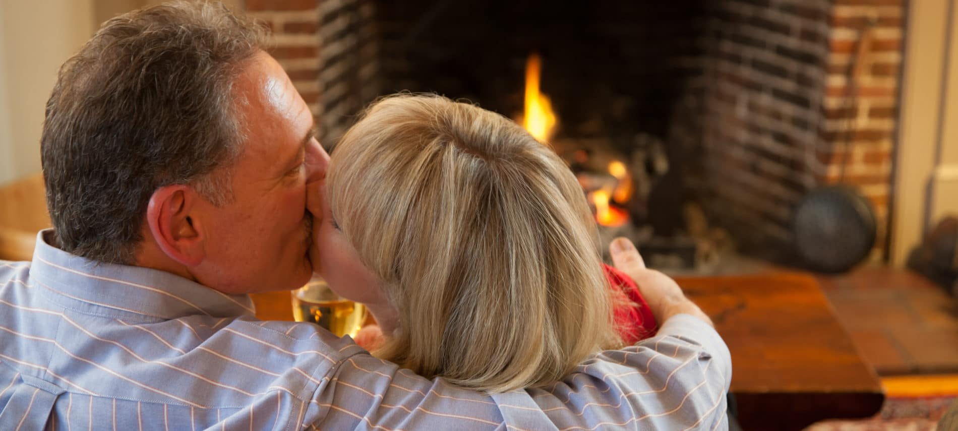 couple kissing in front of a fireplace