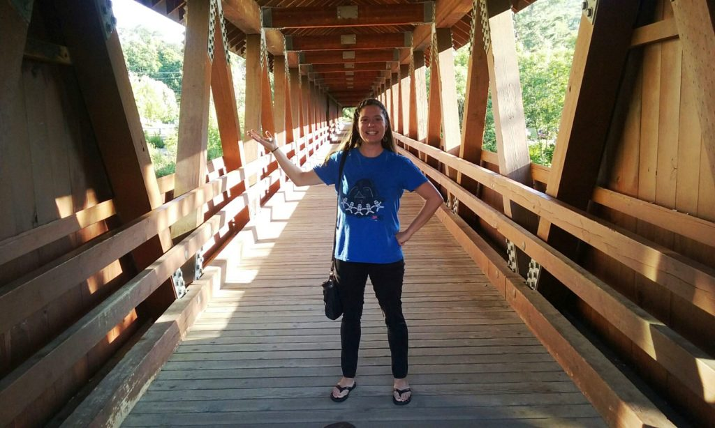 girl standing on a covered bridge