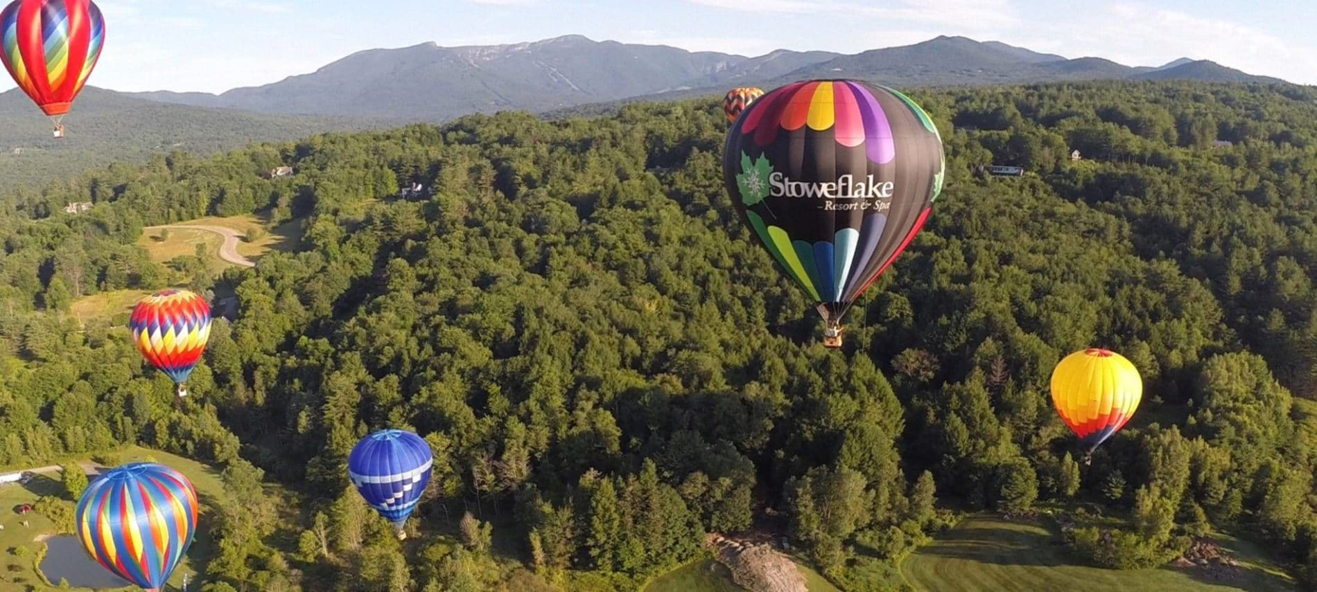 several colorful balloons in the air at the Stoweflake Hot Air Balloon Festival Stowe Vermont