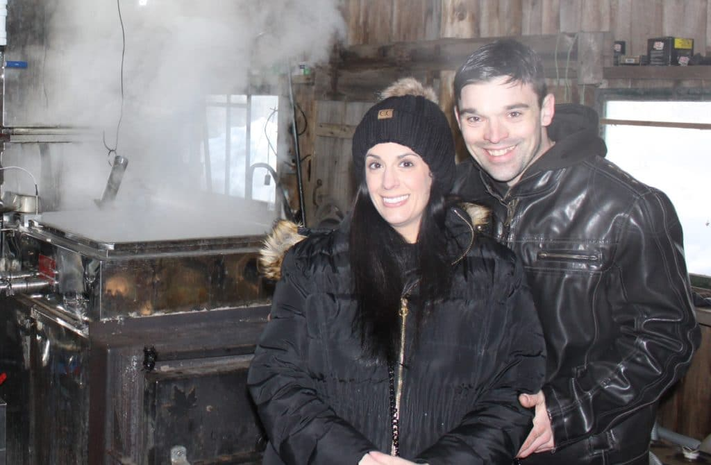 Young couple standing in a maple sugar house with steam from the syrup boiler billowing behind them.