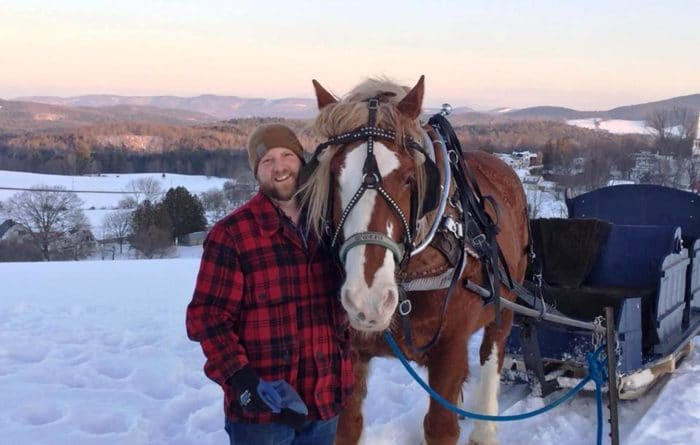 Man standing next to sleigh ride horse