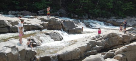 people on the rocks at a Swimming Holes in the White Mountains New Hampshire