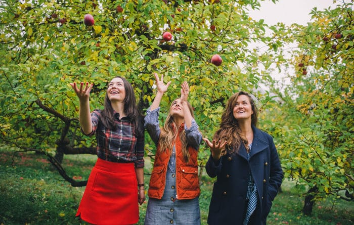 three girls picking apples