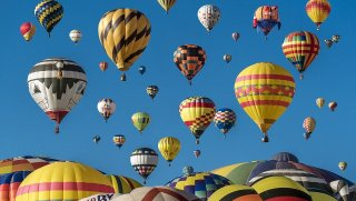 several colorful hot air balloons rising up to a blue sky