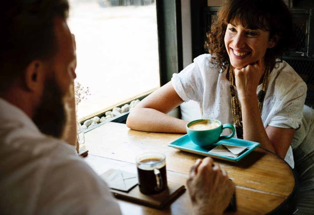 A couple chatting over coffee at a coffee shop