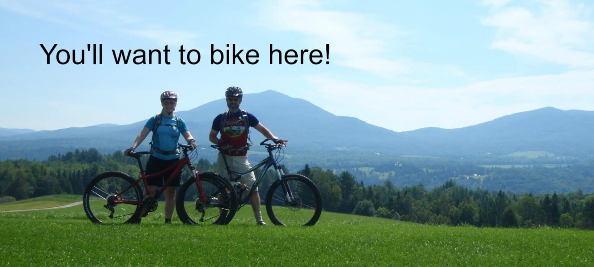 two people standing next to their mountain bikes on a grassy hill.
