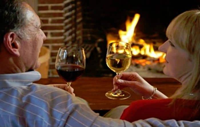 couple toasting each other in front of a fireplace at Rabbit Hill Inn