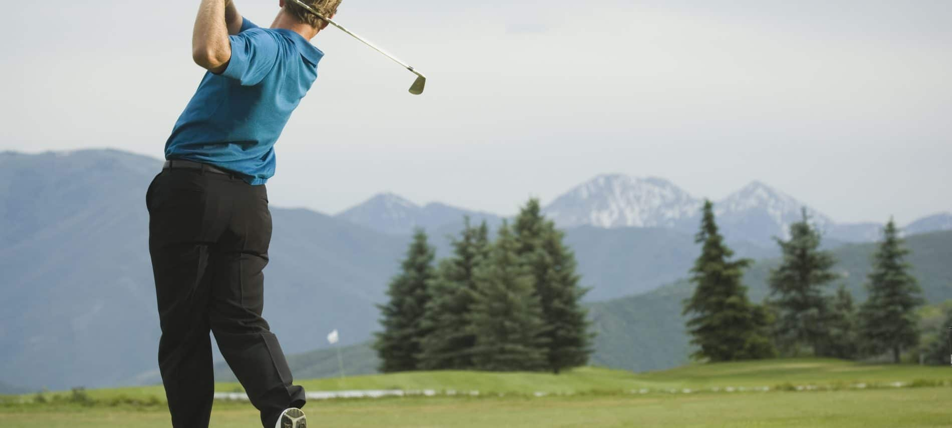 A man swinging a golf club with a backdrop of beautiful mountains