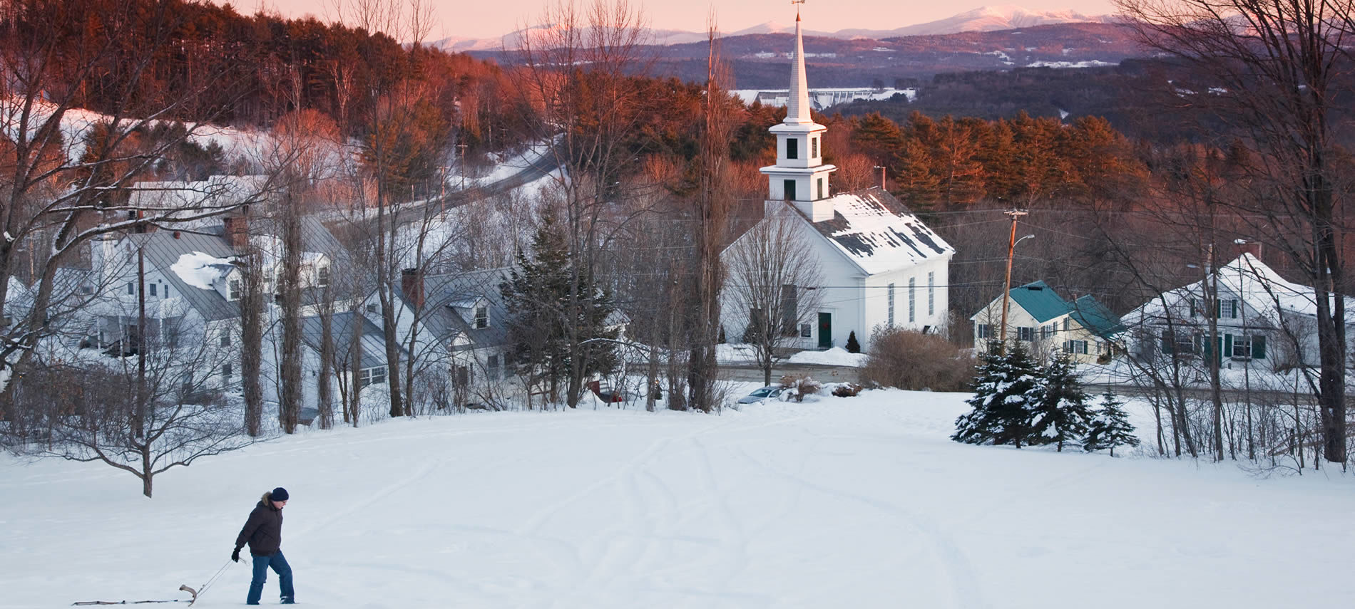 snow covered image of Waterford Village and white steeple church, with a man dragging a sled across the snow