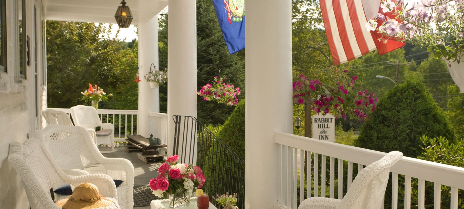 porch with white wicker furniture, pink roses, and lemonade, with flags draping down