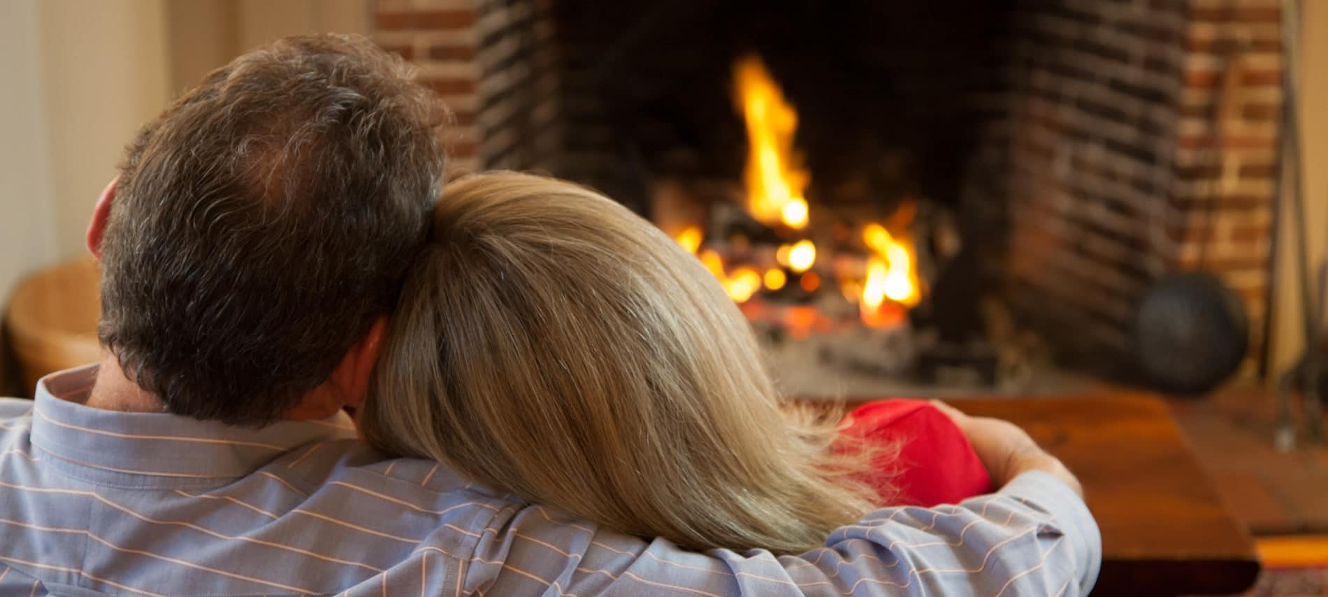 snuggling couple in front of a fireplace