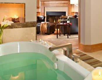 whirlpool tub with fireplace in background