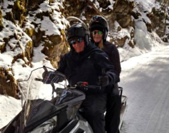couple wearing helmets and goggles on a snowmobile
