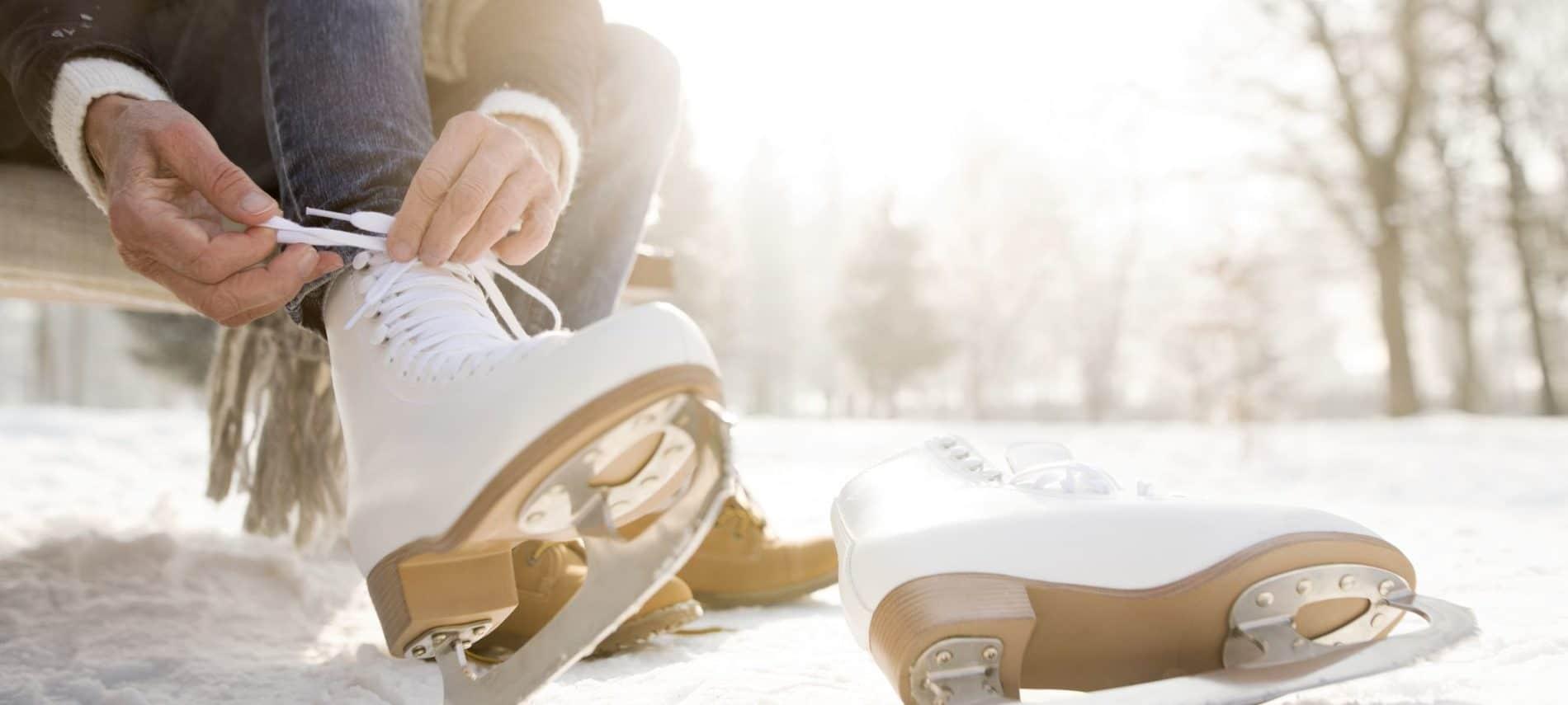 woman tying her white ice skates