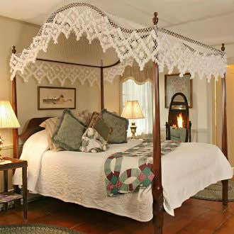 Dark brown wooden post bed with white lace canopy on top, including a white bedspread and green and burgundy quilt with green and cream throw pillows