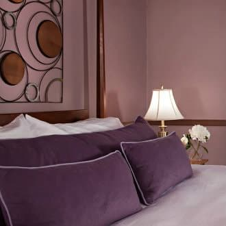 Dark brown wood post bed with white linens and purple pillows