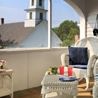 White patio furniture with navy pillows looking out to nearby church