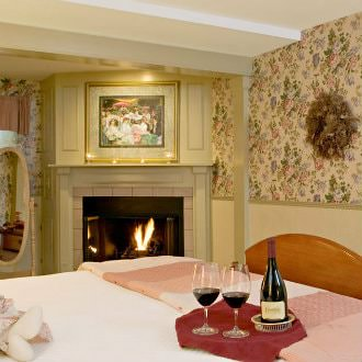 Light brown wooden bed with white linens, shades of pink quilt, and two glasses filled with wine on top of the bed next to a gas fireplace