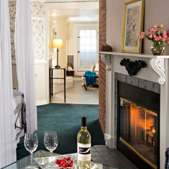 Canopy bed next to gas fireplace with adjoining suite, white wine and red strawberries sit on a nearby table