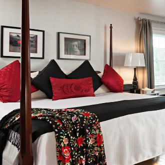 Dark brown wooden four-post bed with white linens, black blanket, and red and black decorative pillows