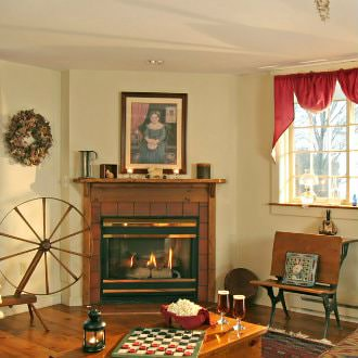 Antique wooden spinning wheel next to a gas fireplace with wooden mantel and wooden table with checker board and popcorn
