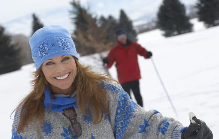 Woman smiling as she enjoys cross country skiing and a man standing in the background