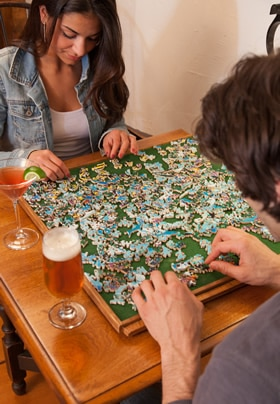Young couple with cocktails completing a Stave Puzzle