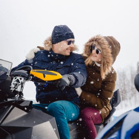 couple on a snowmobile smiling at each other