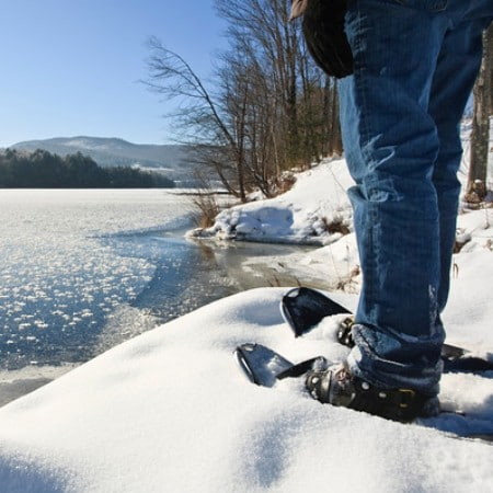 man standing in snowshoes by a river