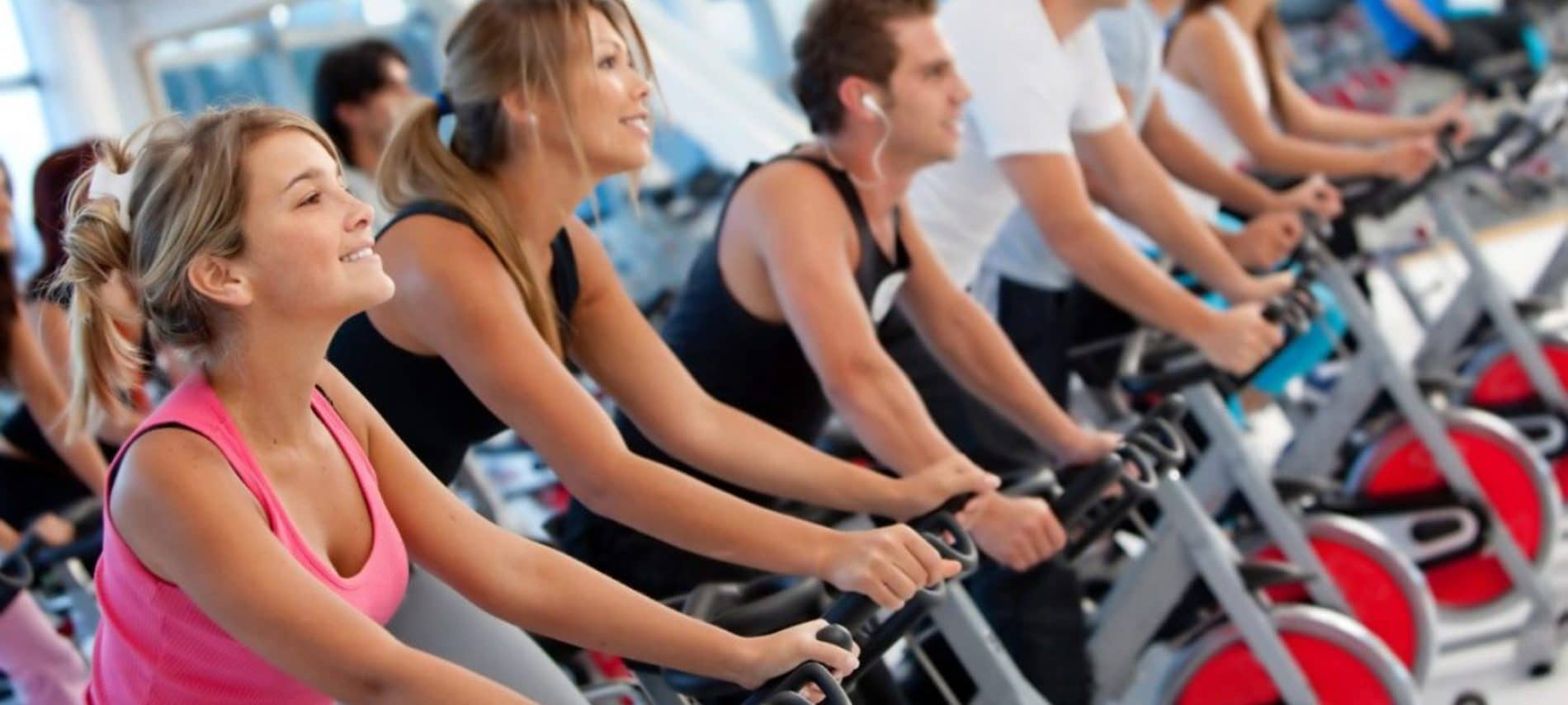group of people riding indoor bikes in a spin class